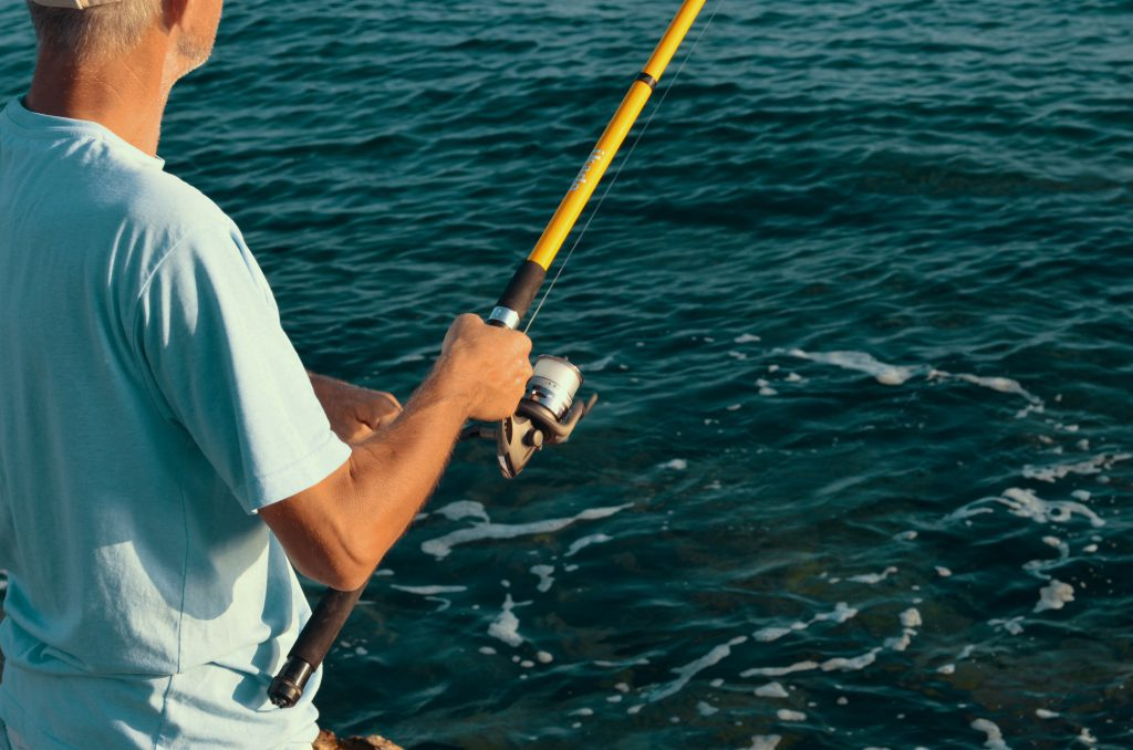 Man catching fish with a spinning rod