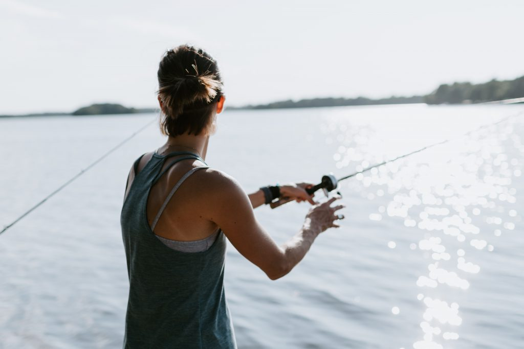Best Crappie Rods - Girl catching fish with fishing rod in hand